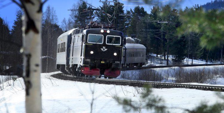 SJ InterCity-tåget kör genom en kurva i vinterlandskap.