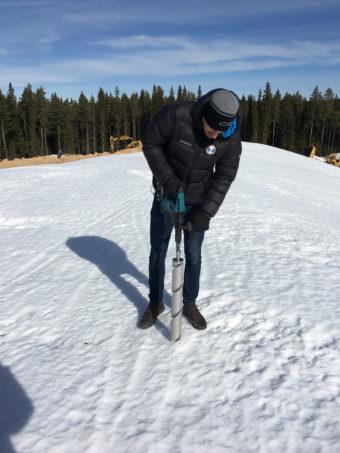 En bild av hur Erik borrar i snön vid Östersunds skidstadion.