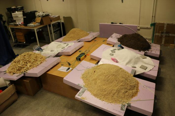 En bild av hur olika täckmaterial, som sågspån och dukar, testas för snölagring.