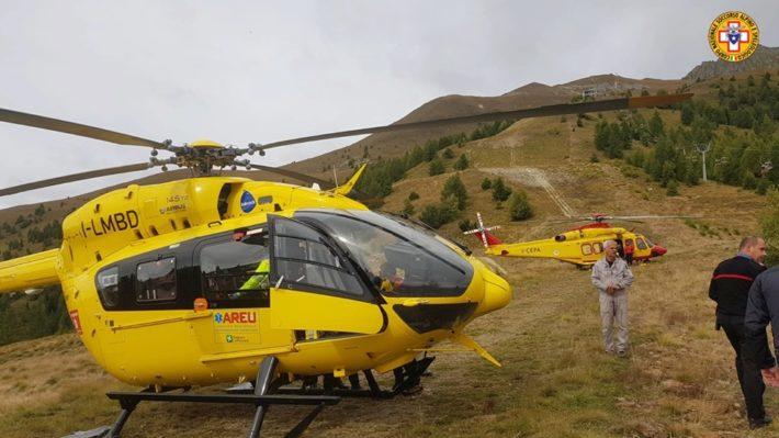 Två gula helikoptrar från den italienska bergsräddningen anländer till olycksplatsen.