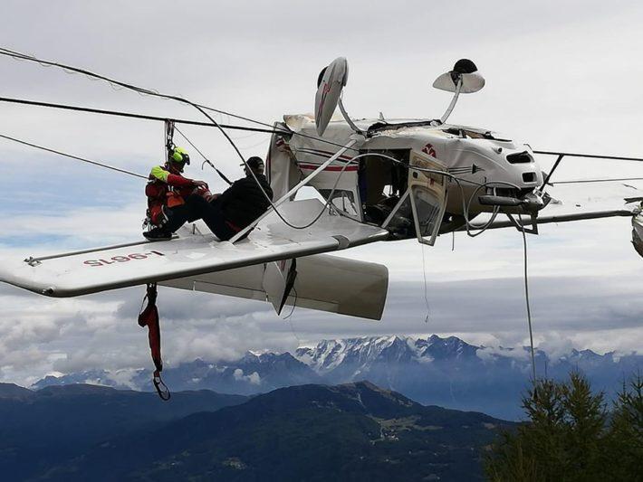 Passageraren sitter på planets vinge medan bergsräddare försöker få ner honom.