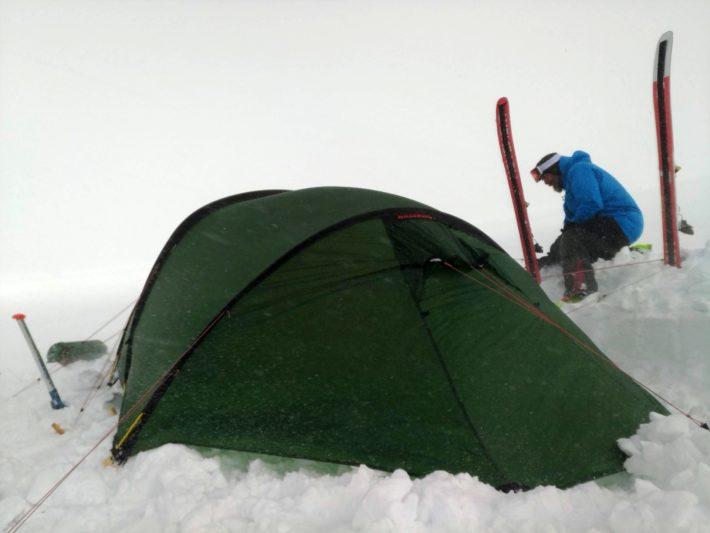 Martin säkrar tältet i snöyran.